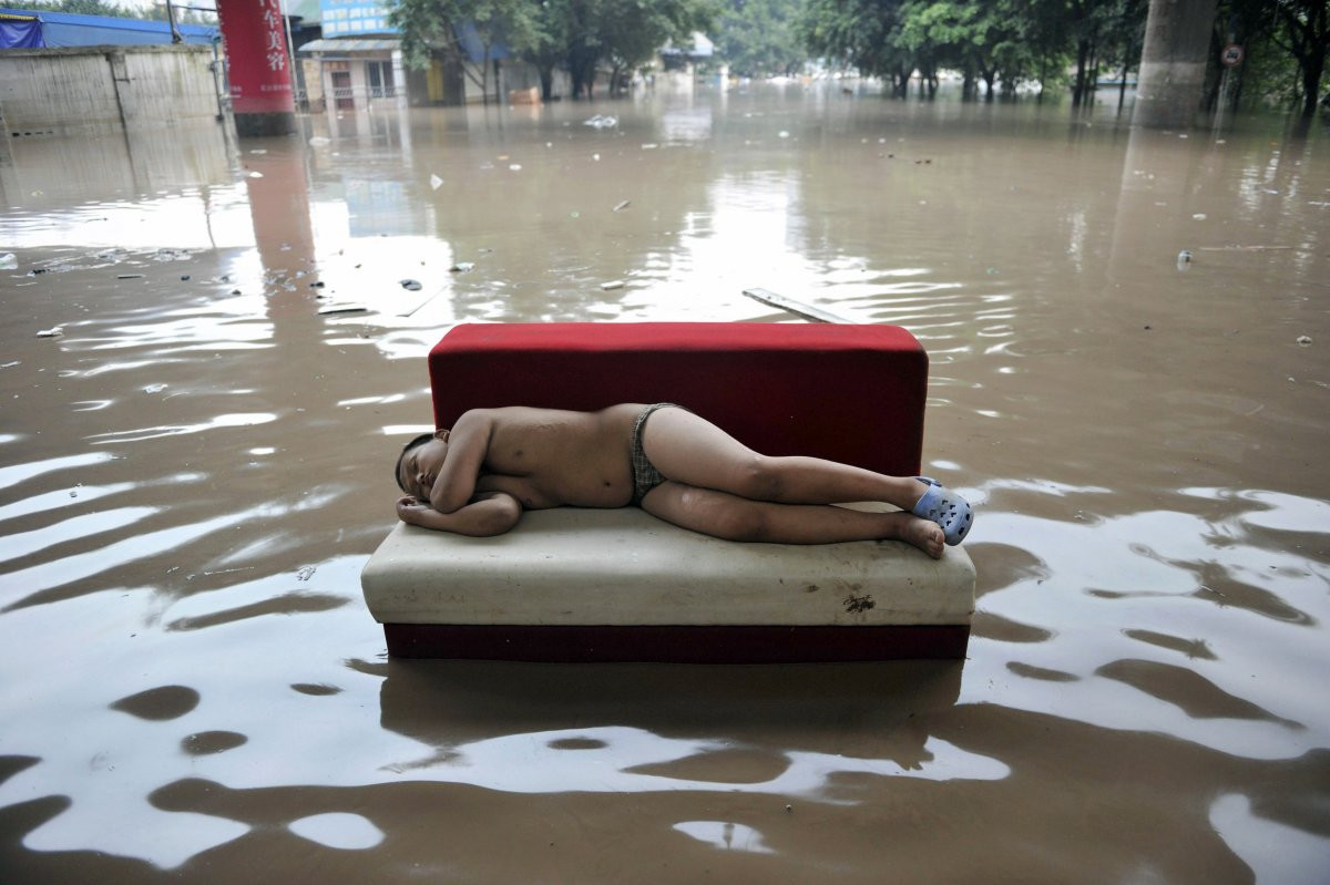 1417178764_and-flooding-isnt-limited-to-the-us-either-here-a-child-sleeps-in-the-middle-of-a-flooded-street-in-chinas-chongqing-municipality-during-a-2010-outbreak-of-torrential-rain-.jpg